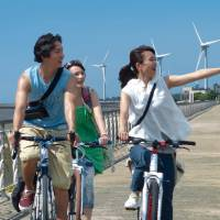 "On the beaten path: Aiko (Mei Kurokawa, right) cycles by Taiwan's tourist sites, guided by Tong Tong (Theresa Daley) in ""Nanpu (Riding the Breeze)."" 