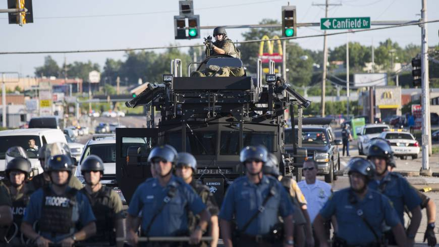 Riot police stand guard as demonstrators protest the shooting death of teenager Michael Brown in Ferguson, Missouri. | REUTERS
