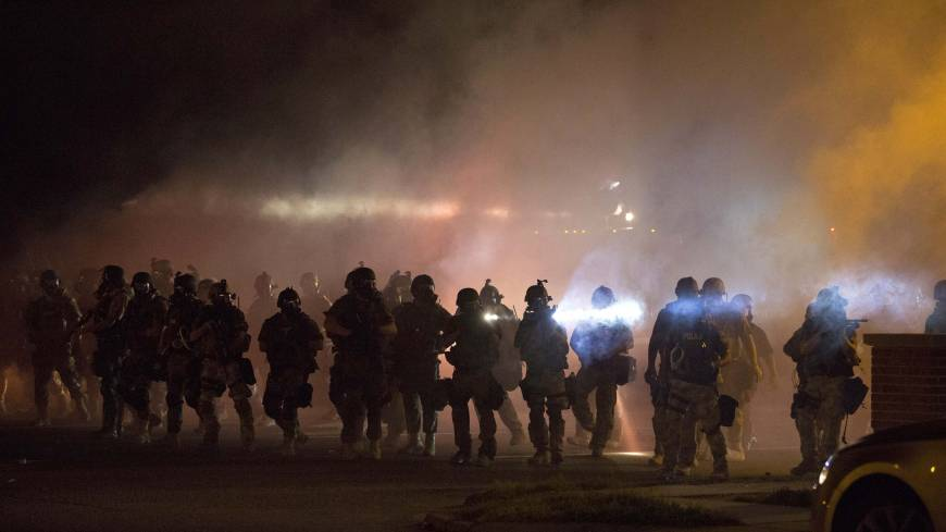 Riot police clear demonstrators from a street in Ferguson, Missouri, Wednesday evening after firing several rounds of tear gas on the fourth night of demonstrations.