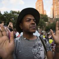 A man holds his hands up during a peaceful demonstration, as communities react to the shooting of Michael Brown in New York's Union Square Park Thursday. | REUTERS