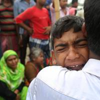A Bangladeshi boy cries for his mother, missing after a ferry they were traveling in capsized Tuesday in the River Padma in Munshiganj district. Rescuers were struggling to locate the ferry that was overloaded and carrying hundreds of passengers when it capsized. | AP