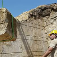 Workers using a crane remove one of the large stone blocks from a wall originally sealing the entrance to an ancient tomb. Archaeologists excavating the large grave mound on Thursday asked politicians and others seeking guided tours of the site to leave them in peace until the dig is completed. | AP