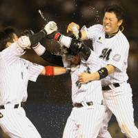 Time to party: Lotte players celebrate after Tatsuhiro Tamura (center) singled home the winning run with two outs in the bottom of the ninth for a walk-off victory over the Buffaloes on Tuesday.    KYODO