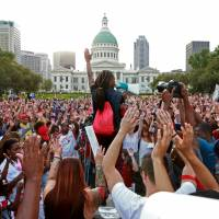 A speaker solicits a response of hands in the air from the crowd Thursday, in St. Louis during a peace vigil and moment of silence for Michael Brown, an unarmed teenager who was shot and killed by Ferguson, Missouri, police Saturday. | AP