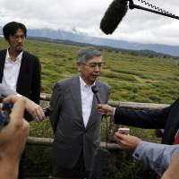 Bank of Japan Gov. Haruhiko Kuroda speaks with reporters during the Jackson Hole Economic Policy Symposium at the Jackson Lake Lodge in Grand Teton National Park near Jackson, Wyoming, on Friday. | AP