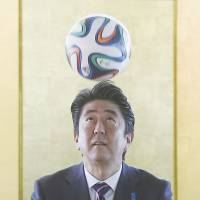 Prime Minister Shinzo Abe heads a soccer ball during a meeting with Brazilian players in Brasilia on Friday. | REUTERS