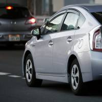 A Prius hybrid made by Toyota Motor Corp. is driven along a street in Tokyo on Feb. 12. | BLOOMBERG