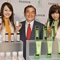 Fujifilm CEO Shigetaka Komori and models show off new skin care products (right) and dietary supplements (left) in Tokyo in September 2006. | AFP-JIJI