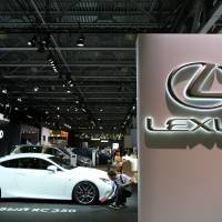 An employee polishes a Lexus RC350 coupe made by Toyota Motor Corp., at the Moscow International Auto Salon on Wednesday.   BLOOMBERG