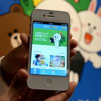 An employee of Line Corp. shows off one of the company's iPhone applications, Line Kids Animation, in March. The messaging app is moving toward a possible dual listing in Tokyo and New York. | AFP-JIJI