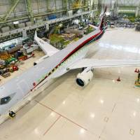 A Mitsubishi Aircraft Corp. Regional Jet sits in a hangar in June in Toyoyama, Aichi Prefecture. Japan Airlines Co. on Thursday announced plans to buy 32 MRJs, in a deal estimated at around ¥150 billion, and to begin using them in 2021 on domestic routes. | MITSUBISHI AIRCRAFT/KYODO