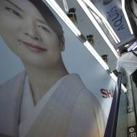 A shopper standing on an escalator rides past advertisements for Sharp Corp.'s Aquos television at an electronics shop in Tokyo on Friday. | REUTERS
