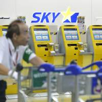 An airport worker pushes carts past the Skymark Airlines check-in counter at Narita International Airport on Wednesday morning. | KYODO