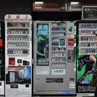 A smoker walks past cigarette machines in Tokyo in April 2012. | BLOOMBERG