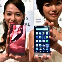 Models display new Sharp smartphones in Tokyo on Monday. Mobile communications giant SoftBank will start selling the Aquos Crystal (right) in Japan on Aug. 29, while subsidiary Sprint will launch it in the U.S. | AFP-JIJI