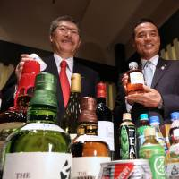 Nobutada Saji (left), chairman and chief executive officer of Suntory Holdings Ltd., and Takeshi Niinami, incoming president, show off some of the company's products during a news conference in Tokyo on July 1. | BLOOMBERG
