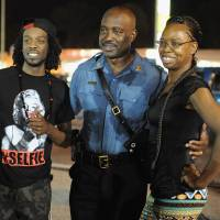 Captain Ron Johnson of the Missouri Highway Patrol takes pictures with demonstrators during a peaceful protest on West Florissant Avenue in Ferguson, Missouri, on Saturday, two weeks after the fatal shooting of Michael Brown. | AFP-JIJI