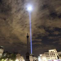 Light is beamed into the sky from London's Trafalgar Square to mark the 100th anniversary of the outbreak of World War I on Monday. | REUTERS