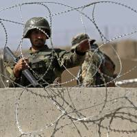 An Afghan National Army soldier keeps watch at the gate of a British-run military training academy Camp Qargha, in Kabul on Tuesday. | REUTERS
