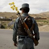 An Afghan National Police officer mans a checkpoint on the outskirts of Maidan Shahr, Wardak province, in May 2013.   AP