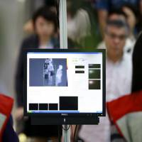 Passengers are screened as they arrive at Yangon International Airport on Wednesday. Asian nations are using thermal imaging cameras and posting doctors at airports to screen out sick travelers as health authorities scramble to avert any outbreak of the Ebola virus that has killed more than 1,000 people in West Africa.   | REUTERS
