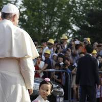 A child walks past Pope Francis after he prayed at the birthplace of St. Andrea Kim Dae-gun, the first Korean-born Catholic priest, at the Solmoe Sanctuary in Dangjin, South Korea, on Friday. Along with China, South Korea is spurring Asia's rise as one of the world's fastest-growing Catholic populations, helping counter slowing growth in Europe and the U.S. | AP