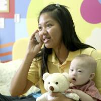 Pattaramon Chanbua, 21, talks on a mobile phone while holding her son Gammy at a hospital in Chonburi province in Thailand on Aug. 3. The Australian government is consulting Thai authorities after news emerged that Gammy, who has Down Syndrome, was abandoned with Chanbua, his surrogate mother, by his Australian parents, who took his healthy twin back home instead, according to local media. | AP