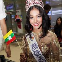 Myanmar model May Myat Noe, winner of the Miss Asia Pacific World 2014 pageant, waves a miniature Myanmar flag upon her arrival June 5 at Yangon International Airport in Myanmar. The first Myanmar national to win an international pageant has been stripped of her title for being rude and dishonest, and has allegedly run off with the expensive crown and breast implants. | AP