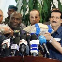 A tv grab taken on July 27 from an AFPTV video shows Malian transport minister Mamadou Hachim Koumare (left) and his Algerian counterpart, Amar Ghoul, holding the black boxes of Air Algerie Flight AH5017 that were retrieved at the crash site in Mali's Gossi region, during a press conference in Bamako. Investigators probing the crash said Thursday they had been unable to access voice recordings from the flight deck. | AFP-JIJI
