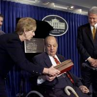 U.S. President Bill Clinton watches as Sarah Brady, gun control advocate and wife of former White House Press Secretary James Brady, takes a plaque from him officially naming the White House briefing room after Brady while their son, Scott, watches at a ceremony at the White House on feb. 11, 2000.  Brady, critically wounded in the 1981 assassination attempt on U.S. President Ronald Reagan, has died, a spokeswoman said Monday. He was 73. | REUTERS