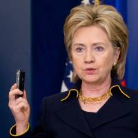 U.S. Secretary of State Hillary Rodham Clinton, appearing at the White House in Washington in May 2009, holds a cellphone as she announces emergency aid for displaced Pakistanis. | AFP-JIJI