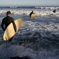 Surfers head toward the waves in the Pacific Palisades section of Los Angeles on Friday.   AP