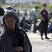 French riot police stand guard as migrants line up during a daily food distribution close to City Hall in Calais northern France, Tuesday. Groups of migrants, mostly Sudanese and Eritreans awaiting departure to the United Kingdom, have been fighting for several days in the port in what resembles a turf war between rival migrant groups.   REUTERS