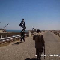 An image taken from video released on Saturday purportedly shows Islamic State militants waving the trademark jihadi flag as they inspect the grounds of the Mosul dam on the Tigris river, about 50 kilometres north of the city. | AFP-JIJI