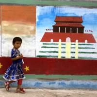 A Uighur child walks past a mural depicting China's Tiananmen Gate on the streets of Aksu in western China's Xinjiang province. The Chinese government uses expansive controls and propaganda to maintain a virtual monopoly on the narrative in the tense region of Xinjiang, where minority Uighurs complain of oppression under Beijing's rule. | AP
