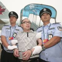 Chinese fugitive Lai Changxing is escorted back to Beijing from Canada at Beijing International Airport on July 23, 2011. | REUTERS