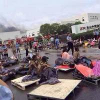 Rescuers help the victims of an explosion at the gate of a factory in Kunshan, in China's Jiangsu province, on Saturday. A factory blast in the eastern industrial province killed at least 65 people, state media reported. | REUTERS