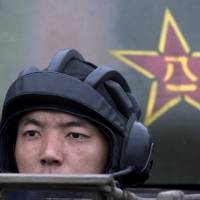 A Chinese People's Liberation Army cadet takes part in a tank demonstration at the PLA's Armored Forces Engineering Academy on the outskirts of Beijing on July 22. | AP