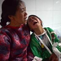 An injured girl cries in the corridor of Ludian hospital Monday after a 6.1-magnitude earthquake hit Ludian County in Zhaotong, southwest China, a day earlier. | AFP-JIJI