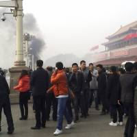 Smoke rises in front of the main entrance of the Forbidden City in Beijing on Oct. 28, 2013, following what China termed a 'terrorist' attack. | REUTERS