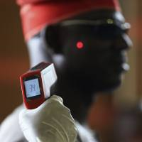 Authorities at Nnamdi Azikiwe International Airport in Abuja, Nigeria, are using remote thermometers to check the health of arriving passengers. Ten cases of Ebola have been reported in Lagos, with two deaths. The Liberian government, struggling with hundreds dead, says it will soon receive experimental drugs. | REUTERS