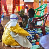 An MSF medical worker feeds an Ebola child victim at an MSF facility in Kailahun, Sierra Leone, on Aug. 15. Kailahun along with Kenama district is at the epicenter of the world's worst Ebola outbreak. Health organizations are looking into the possible use of experimental drugs to combat the latest outbreak in West Africa. | AFP-JIJI