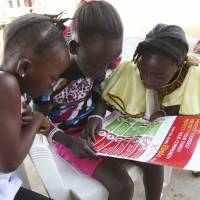 Girls look at a UNICEF poster with information and illustrations on the best practices to help prevent the spread of Ebola, in Voinjama, Liberia, in April. | REUTERS