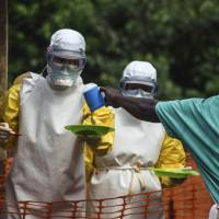 Medical staff with Doctors Without Borders prepare to bring food to patients kept in an isolation area at an Ebola treatment center in Kailahun, Sierra Leone, on July 20. | REUTERS