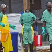 Health care workers in their Ebola virus protective gear are photographed at a treatment center in Monrovia on Monday. | AP