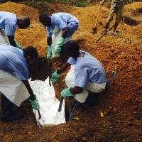 Volunteers lower the corpse of an Ebola victim — prepared according to strict burial guidelines designed to curb contamination risks — into a grave in Kailahun, Sierra Leone, on Saturday. | REUTERS