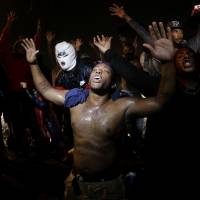 People defy a curfew Sunday to protest the death of teenager Michael Brown at the hands of local police in Ferguson, Missouri, last Saturday. Brown's shooting in the middle of a street following a suspected robbery of a box of cigars from a nearby market has sparked a week of protests, riots and looting in the St. Louis suburb. | AP