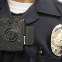 A Los Angeles Police officer wears an on-body camera during a demonstration for media in January 2015. The fatal police shooting of an unarmed black teenager in Ferguson has prompted calls for more widespread use of the lapel-mounted devices, which record interactions between the public and law enforcement. | AP
