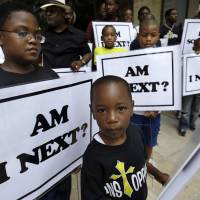 Alvin Duplessis, 10, (left), and Thomas McGriff, 5, (foreground), hold signs with others from the Watson Memorial Teaching Ministries Church of New Orleans at a rally held in the city on July 20, 2014 following the acquittal of George Zimmerman in the shooting death of Trayvon Martin. | AP