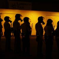 Police wait to advance after tear gas was used to disperse a crowd in Ferguson, Missouri, on Sunday during a protest over the death of Michael Brown, who was killed by a police officer in the city on Aug. 9. | AP
